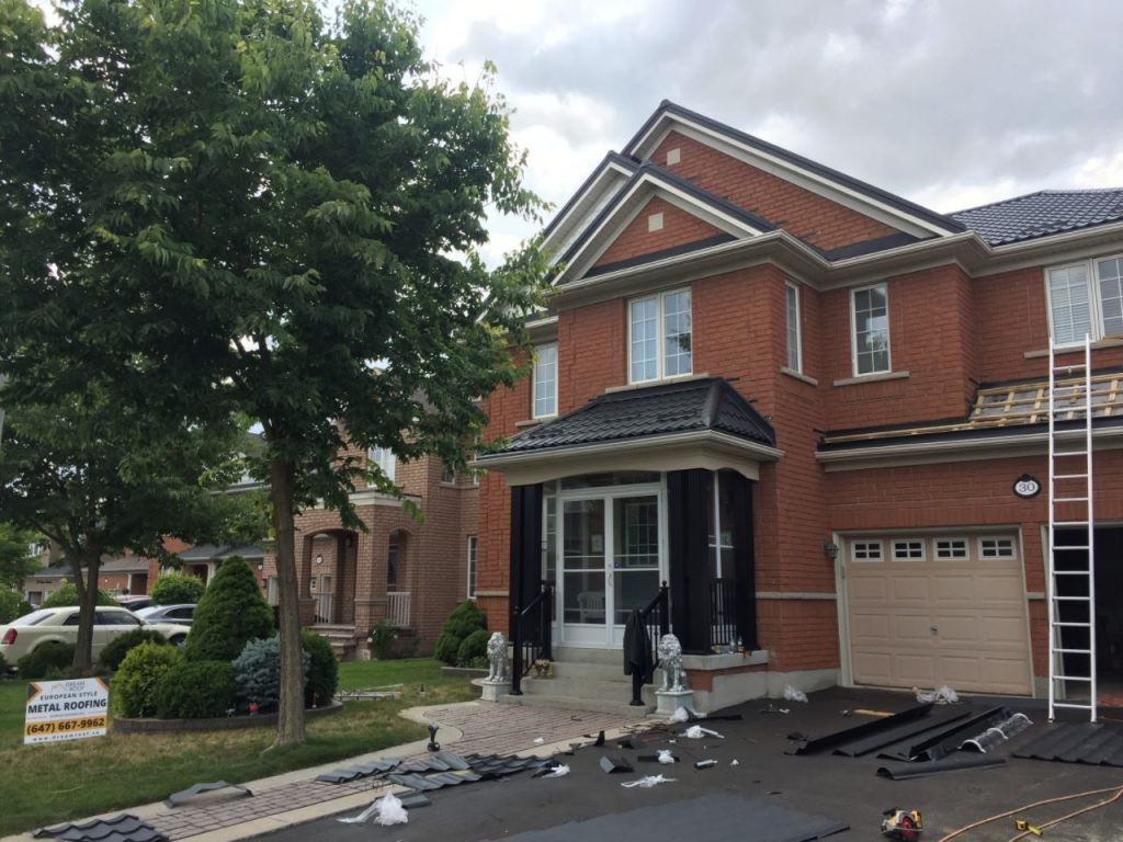 Black roof installation on red brick house
